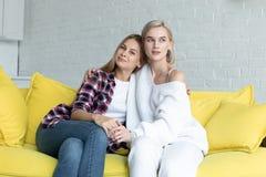 Retrato de pares lesbianos hermosos en la ropa casual que abraza, sent?ndose en el sof? amarillo en casa fotos de archivo