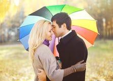 Retrato de pares loving novos com o guarda-chuva colorido que abraça o outono imagens de stock