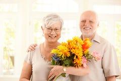 Retrato de pares mayores felices con las flores Imagenes de archivo