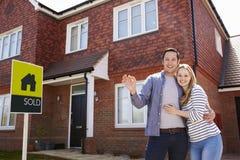 Retrato de pares novos com chaves à casa nova imagem de stock