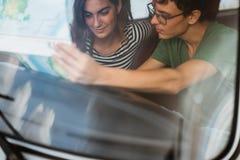 Retrato de pares novos dentro do carro usando um mapa fotos de stock royalty free