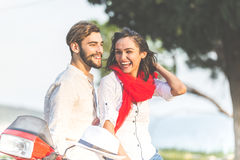 Retrato de pares novos felizes do amor no 'trotinette' que aprecia-se em um parque em horas de verão Imagens de Stock Royalty Free