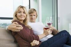 Retrato de pares sonrientes con las copas de vino en sala de estar en casa Fotos de archivo