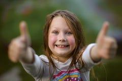 Retrato de poco hermoso y de la muchacha confiada que muestra los pulgares Foto de archivo libre de regalías