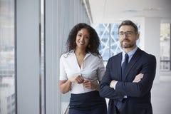 Retrato de proprietários empresariais novos no escritório vazio imagem de stock