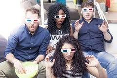 Retrato de quatro adultos novos que vestem os vidros 3d em casa Imagem de Stock