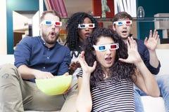 Retrato de quatro adultos novos que vestem os vidros 3d em casa Fotografia de Stock