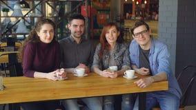 Retrato de quatro amigos dos jovens na roupa ocasional que senta-se na tabela no café espaçoso com copos de chá e que olha filme