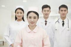 Retrato de quatro trabalhadores de sorriso dos cuidados médicos que olham a câmera, no hospital, China imagem de stock royalty free