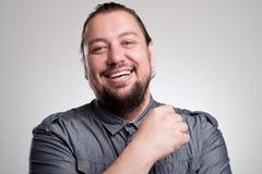 Retrato de reír al hombre joven contra la pared gris Sonrisa feliz del individuo Foto de archivo libre de regalías