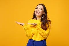 Retrato de reír a la mujer joven en el suéter, pantalones azules que miran la cámara señalando las manos a un lado aisladas en am fotos de archivo libres de regalías