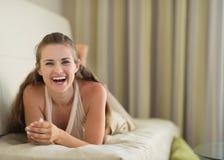 Retrato de reír a la mujer joven que pone en el diván fotos de archivo