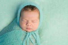 Retrato de recién nacido soñoliento con la cabeza y el cuerpo envueltos Imagen de archivo libre de regalías