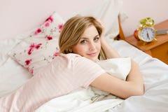Retrato de relaxar a mulher loura nova feliz bonita na cama com despertador Fotografia de Stock
