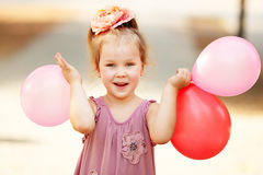 Retrato de rir e de jogar a menina do aniversário que guarda balões imagens de stock royalty free