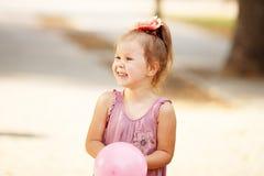 Retrato de rir e de jogar uma menina que guarda um balão foto de stock royalty free
