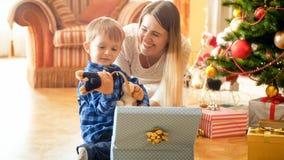 Retrato de rir a mãe nova com os presentes de sorriso pequenos do Natal da abertura do menino fotografia de stock royalty free