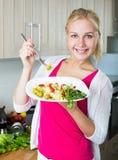 Retrato de rir a menina loura que come a salada imagem de stock
