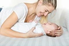 Retrato de rir 3 meses de bebê idoso e jovem mulher que encontram-se na cama Imagem de Stock