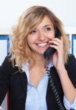 Retrato de rir a mulher de negócios loura no escritório no telefone fotografia de stock