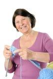 Retrato de rir a mulher idosa com fio e agulha de confecção de malhas imagem de stock