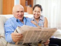 Retrato de rir a mulher madura e o homem idoso com jornal foto de stock royalty free