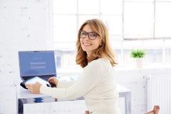 Retrato de rir a mulher de negócios madura que senta-se na mesa de escritório e que usa sua tabuleta digital imagens de stock