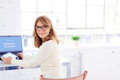 Retrato de rir a mulher de negócios madura que senta-se na mesa de escritório e que usa sua tabuleta digital fotos de stock