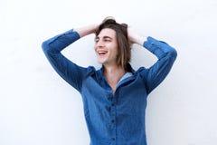 Retrato de rir o homem considerável com mãos no cabelo longo foto de stock