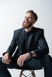Retrato de rir o homem farpado à moda que senta-se na cadeira fotos de stock royalty free