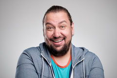 Retrato de rir o homem novo contra a parede cinzenta Sorriso feliz do indivíduo fotografia de stock royalty free