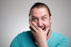 Retrato de rir o homem novo contra a parede cinzenta Sorriso feliz do indivíduo foto de stock