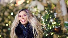 Retrato de rir o levantamento bonito da mulher cercado por flocos de neve no bokeh das luzes da árvore de Natal vídeos de arquivo