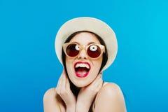 Retrato de rir o modelo fêmea em óculos de sol da forma e em chapéu do verão no fundo azul foto de stock