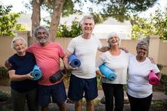Retrato de rir os amigos superiores que levam esteiras do exercício no parque foto de stock royalty free