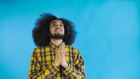 Retrato de rogar al individuo afroamericano que mantiene los fingeres por favor cruzado y de griterío dios en fondo azul Concepto almacen de metraje de vídeo