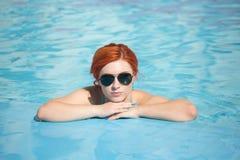 Retrato de salir hermoso de la mujer de una piscina el pelo largo hermoso bronceó la presentación modelo por el agua azul de la p Foto de archivo libre de regalías