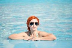 Retrato de salir hermoso de la mujer de una piscina el pelo largo hermoso bronceó la presentación modelo por el agua azul de la p Imagen de archivo