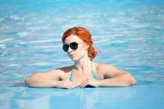 Retrato de salir hermoso de la mujer de una piscina el pelo largo hermoso bronceó la presentación modelo por el agua azul de la p Imagenes de archivo
