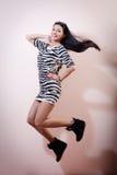 Retrato de saltar a jovem mulher moreno magro bonita no vestido da zebra e nos risos abafados sorriso feliz & de olhar a imagem d Fotografia de Stock