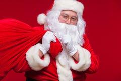 Retrato de Santa Claus com o saco vermelho enorme que mantém o dedo indicador por sua boca e que olha a câmera Imagens de Stock