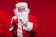 Retrato de Santa Claus com o saco vermelho enorme que mantém o dedo indicador por sua boca e que olha a câmera Fotos de Stock Royalty Free
