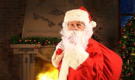 Retrato de Santa Claus com o saco vermelho enorme que mantém o dedo indicador por sua boca e que olha a câmera Imagens de Stock Royalty Free