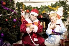 Retrato de Santa Claus con la doncella de la nieve en el árbol de Cristmas que sostiene los regalos Foto de archivo