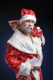 Retrato de Santa, que guarda o dinheiro em um fundo azul imagem de stock royalty free