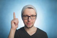 Retrato de señalar sonriente del hombre joven ascendente mientras que se opone a fondo azul Tiro vertical imagenes de archivo