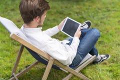 Retrato de sentar al hombre joven en hierba con la tableta digital Fotos de archivo libres de regalías