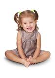 Retrato de sentar a menina irritada da criança com sorrir forçadamente isolada no branco Foto de Stock