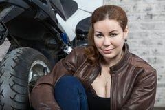 Retrato de sentarse del motorista de la mujer joven interior delante de su moto Imagen de archivo