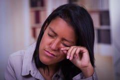 Retrato de sentarse deprimido del adolescente limpio su cara de un rasgón, mujer joven triste subrayada que tiene problemas menta Fotos de archivo libres de regalías